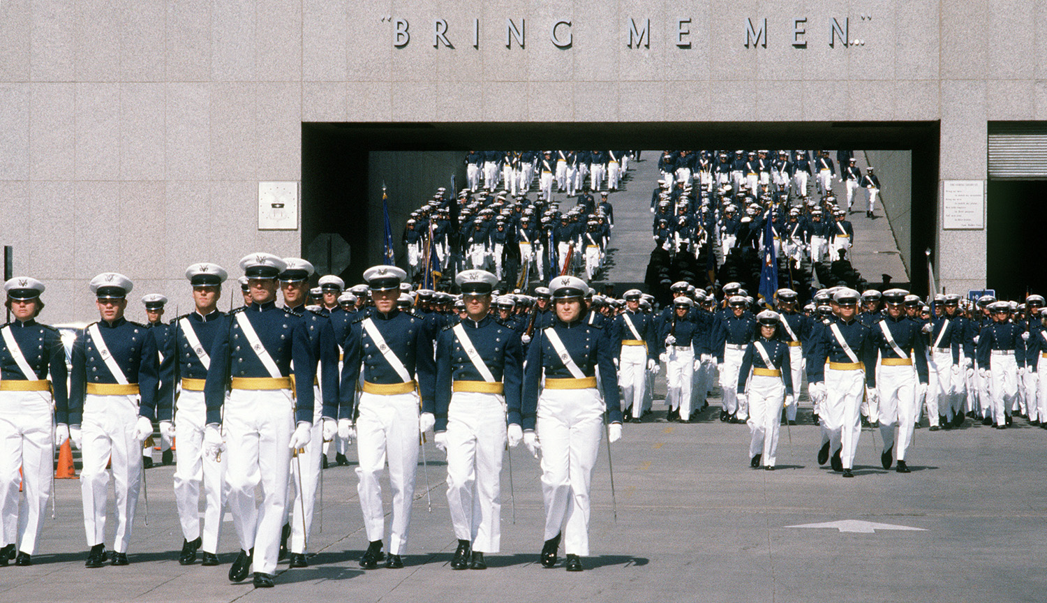 Color image of mostly white, largely male-presenting Air Force cadets in dress uniform parading in formation through an open passageway. Text over the passageway reads: Bring Me Men.