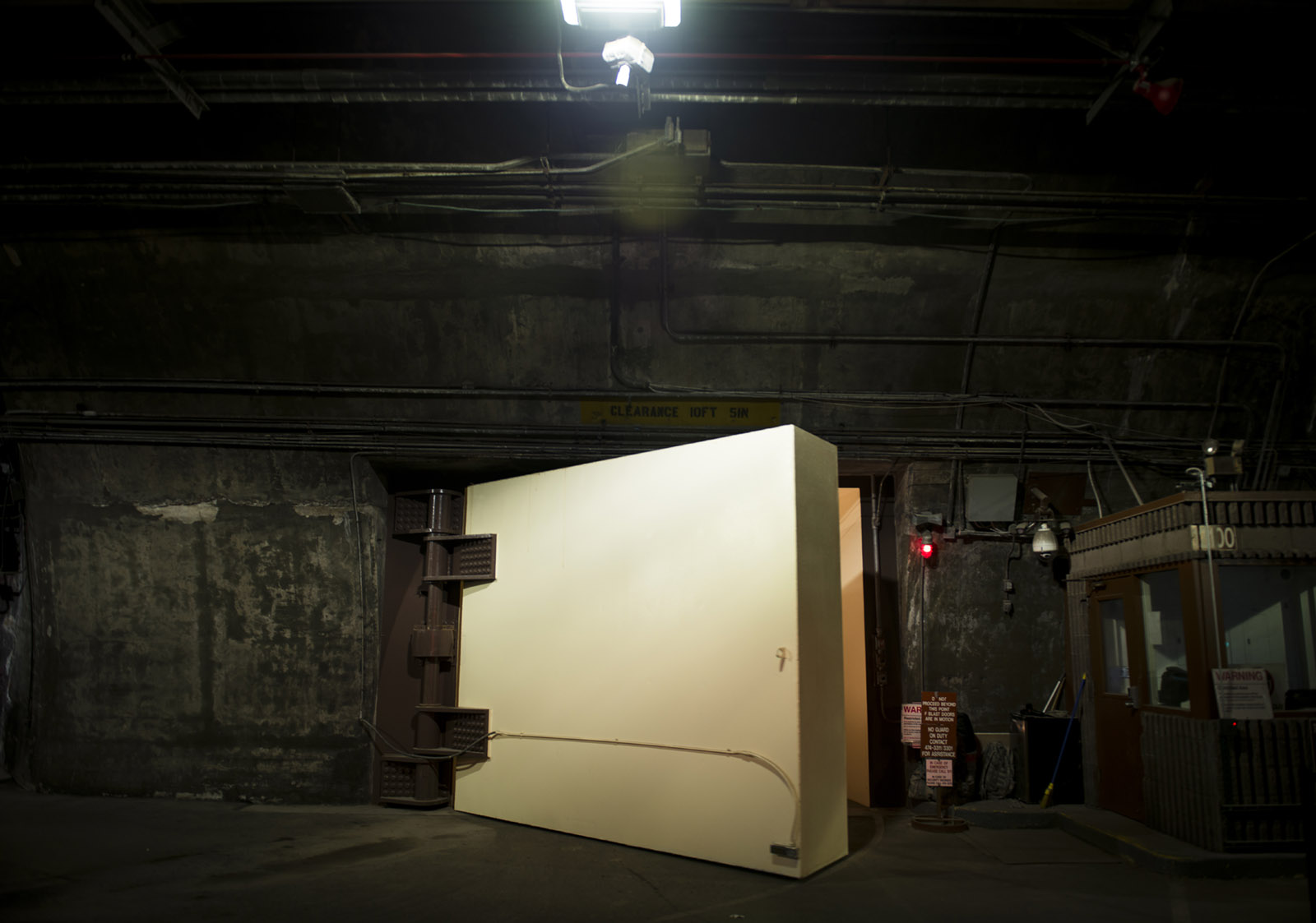 A very thick, large, cream-colored, metal door stands ajar in a dimly lit, underground cavern whose walls are covered in metal sheeting and piping.