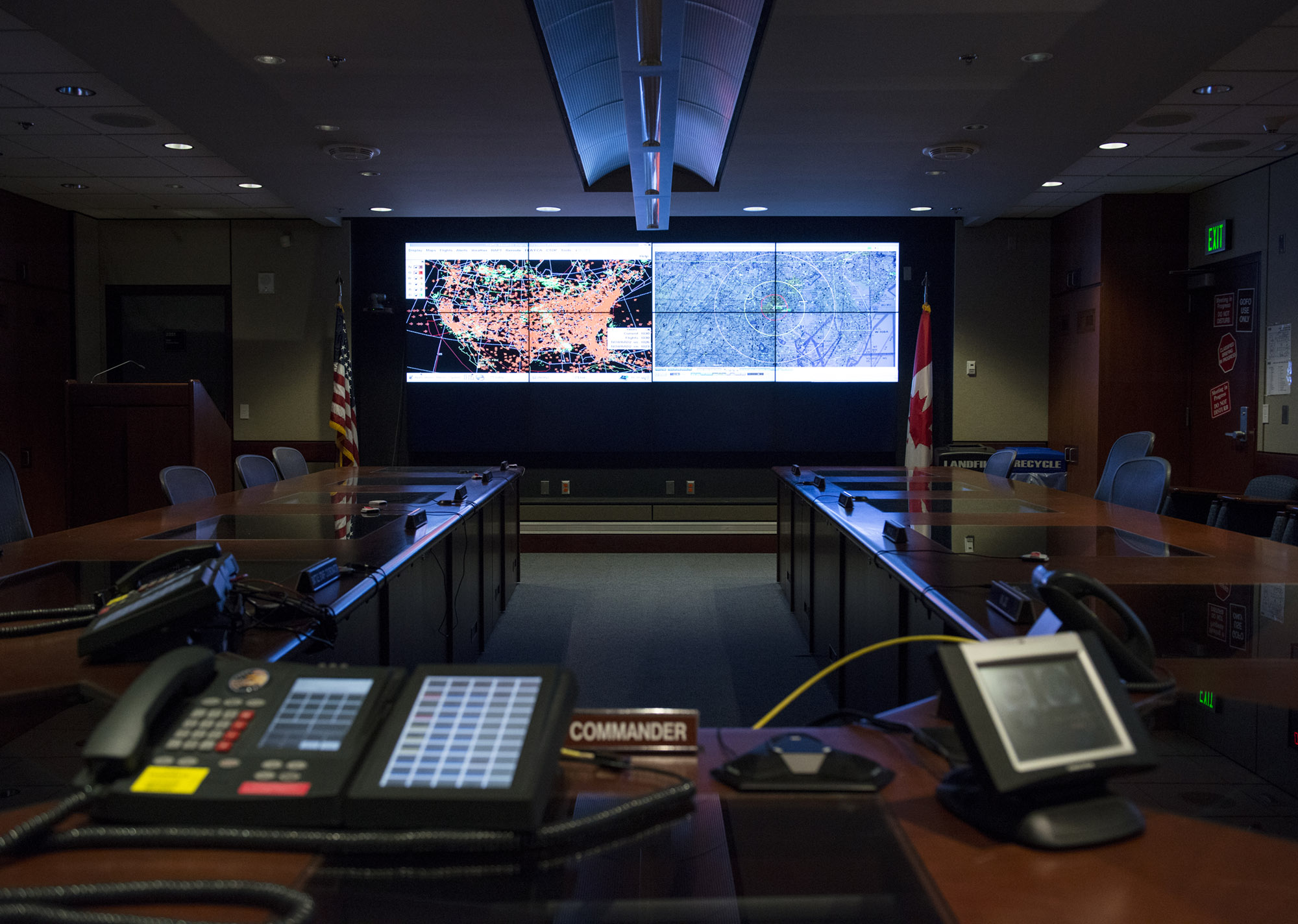 A conference room lit up by two large screens. The one on the left shows air traffic in the continental United States, while the one on the right shows a detail view of terrain. In the foreground is a desk marked