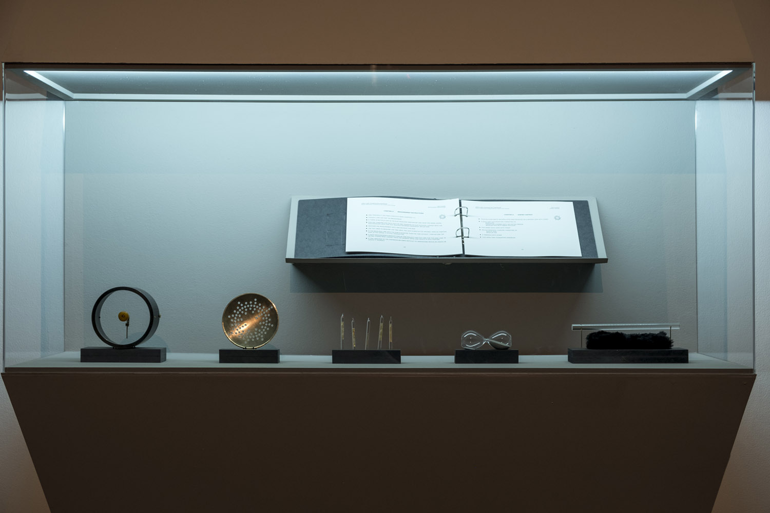 Installation of instrument-like objects and documents in a museum vitrine
