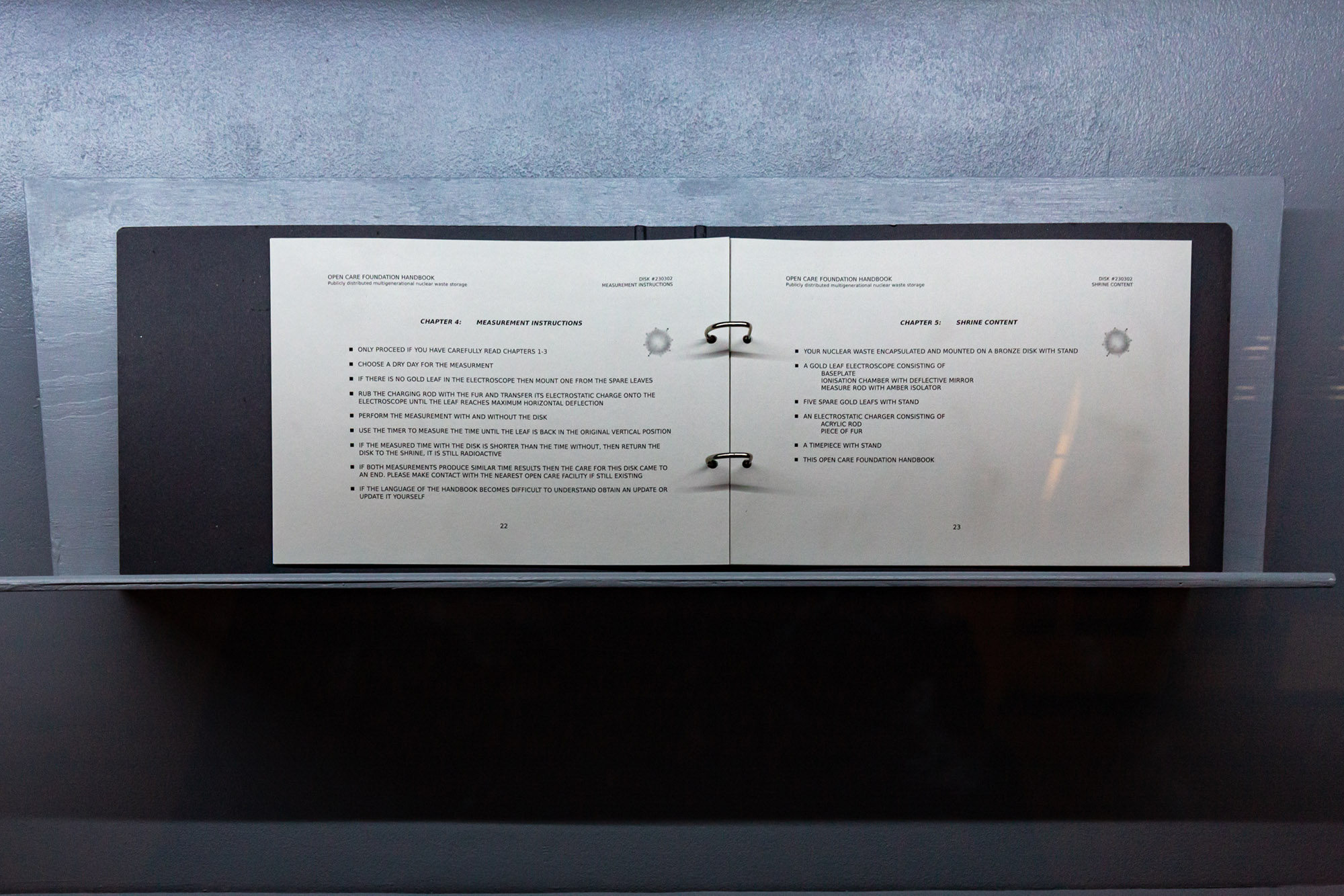 Close up of installation object consisting of two-ring binder and text documents