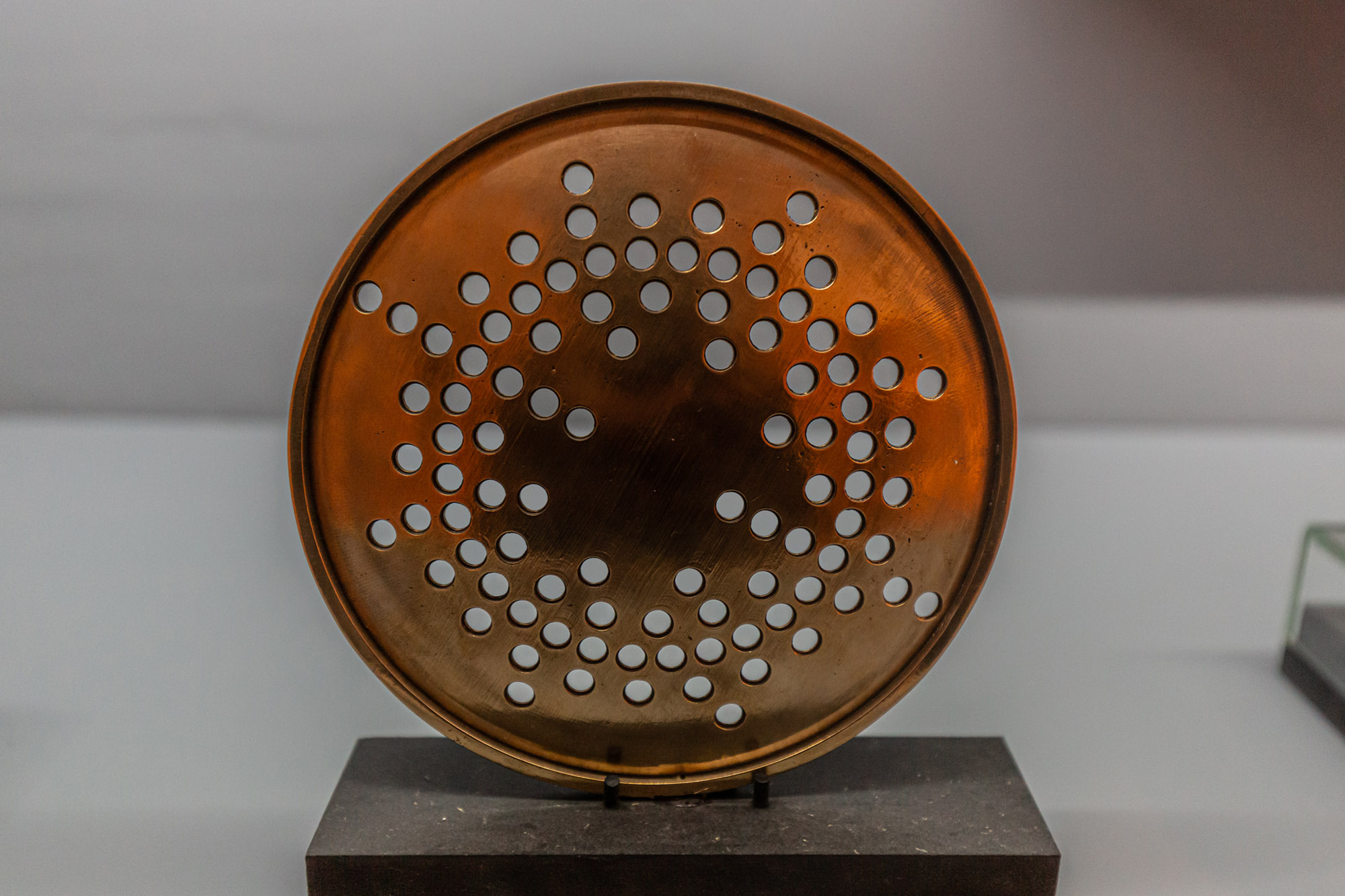 Close up of installation object consisting of a bronze disk with small drilled holes in an irregular circular pattern mirroring that of the