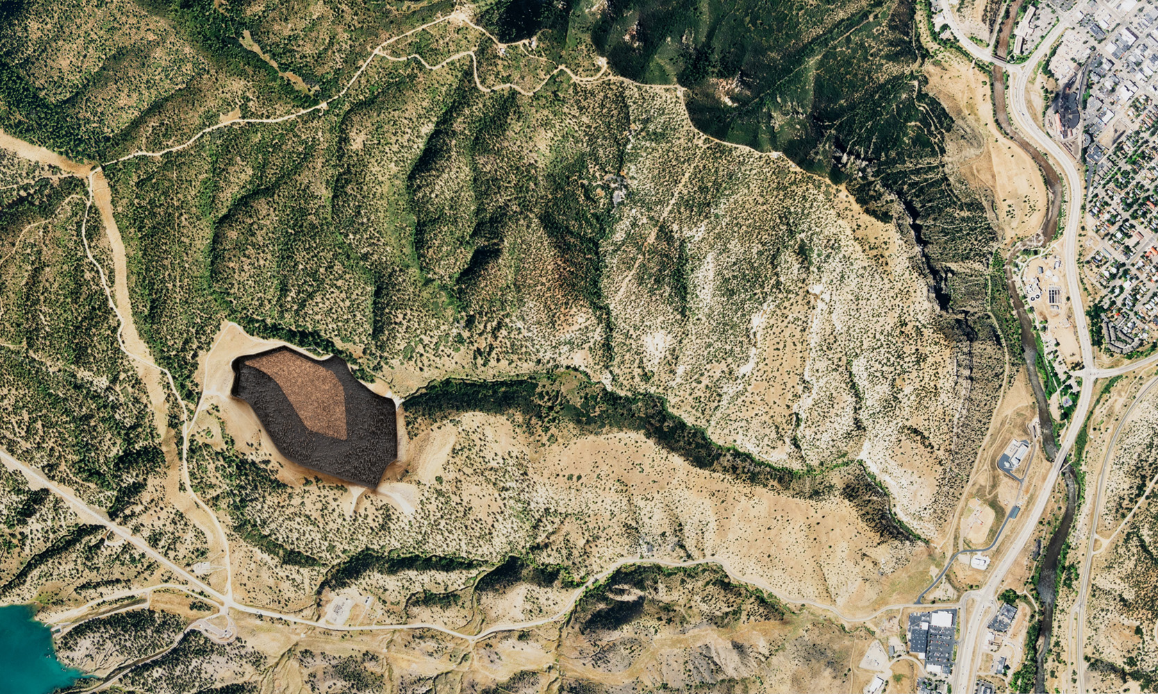 Aerial view of an arid landscape, An irregular form in the left-center portion of the composition is burnt into the surface of the image.