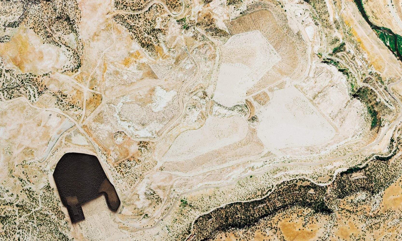 Aerial view of an arid landscape, An irregular form in the lower left hand portion of the composition is burnt into the surface of the image.