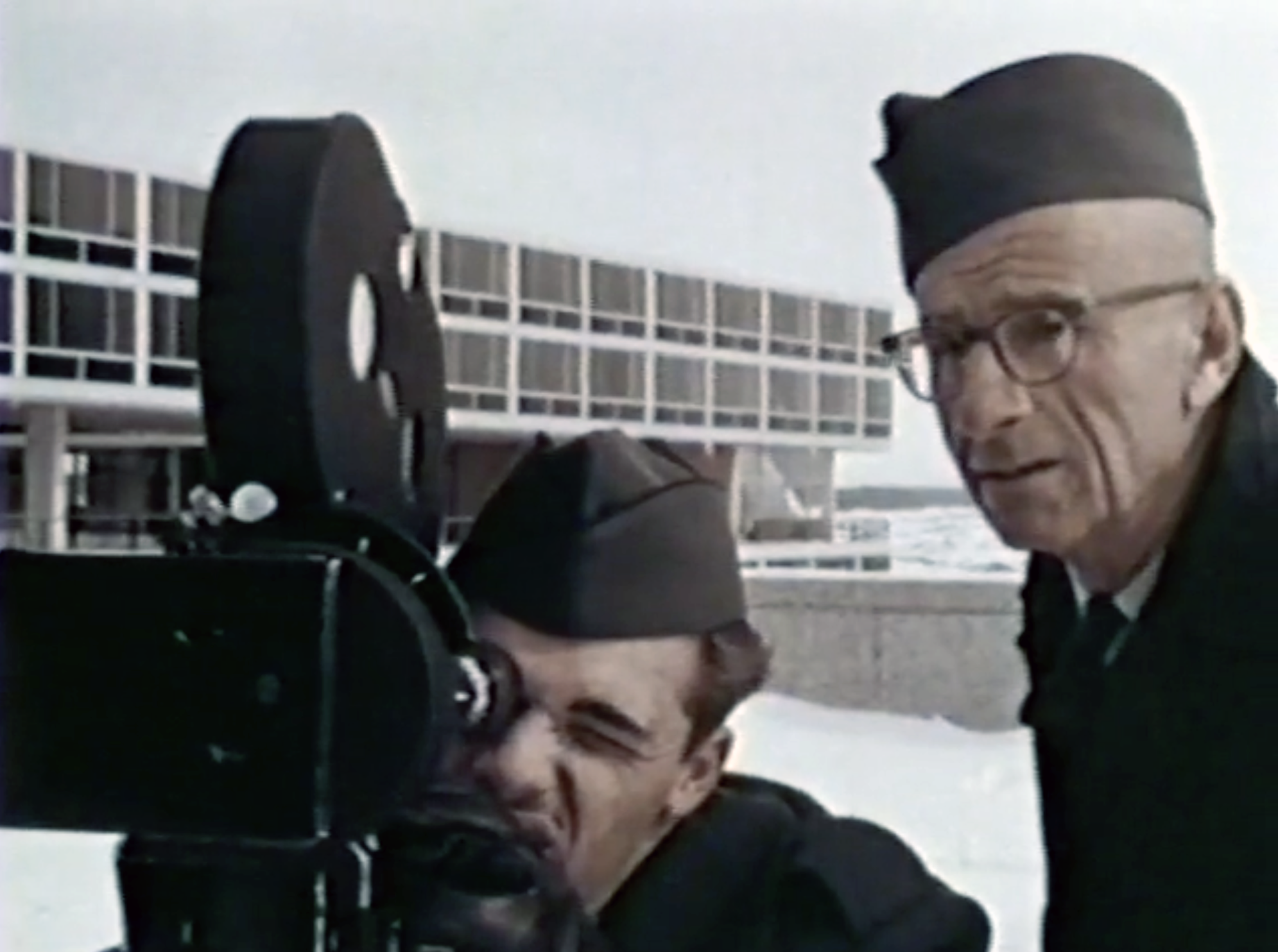 Soft-focus image of two White- and male-presenting people in military uniform operating a film camera. A modernist building from the U.S. Air Force Academy campus is in the background