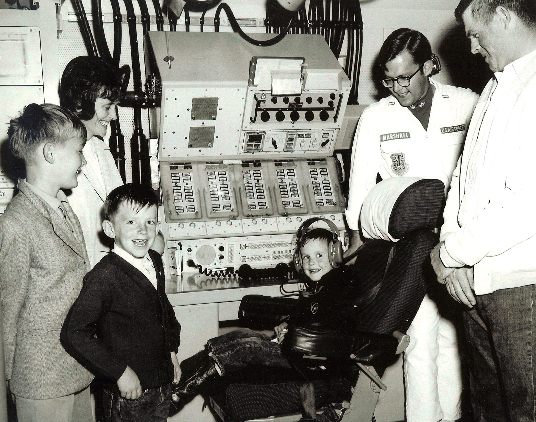 A white-presenting family with mother, father, and three young boys poses by a control panel with a technician in a white robe. The youngest child sits in the commander seat.