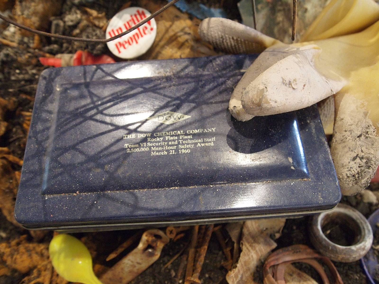 Installation detail showing a blue metal plaque from the Dow Chemical Company awarding Team 6 a 1960 safety award. A dirty rubber glove and and other detritus, including a soft-focus activist pin reading