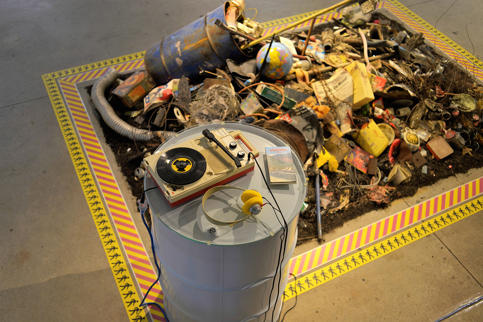 A vintage plastic record player sits on a waste drum amidst an installation of debris.