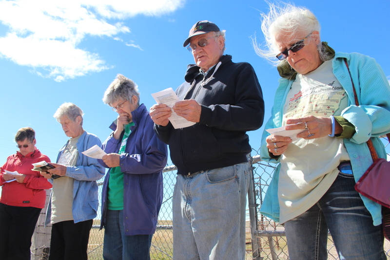 Low-angle image showing five elderly white-presenting people reading from a sheet of paper in a semi-circle before a chain link fence in a flat, arid landscape.
